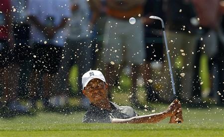 Tiger Woods of the U.S. hits from a sand trap on the 17th hole during first round play in the 2012 Masters Golf Tournament at the Augusta National Golf Club in Augusta